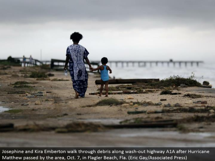 Josephine and Kira Emberton stroll through flotsam and jetsam along wash-out interstate A1A after Hurricane Matthew went by the range, Oct. 7, in Flagler Beach, Fla. (Eric Gay/Associated Press)