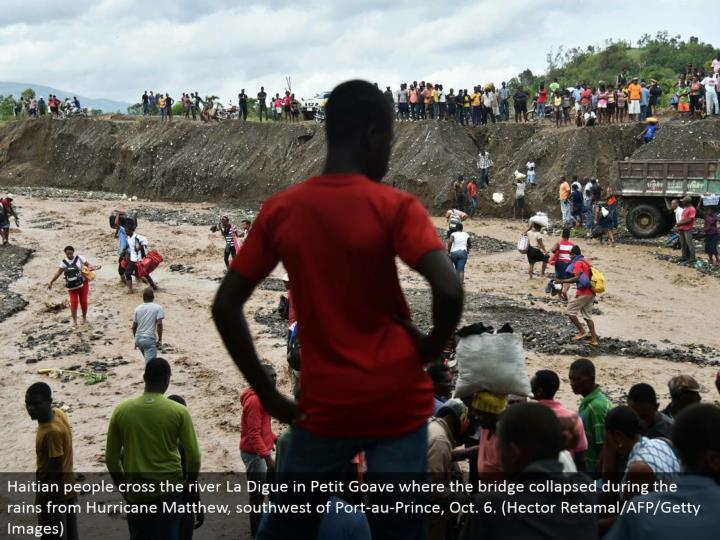 Haitian individuals cross the stream La Digue in Petit Goave where the extension broken down amid the downpours from Hurricane Matthew, southwest of Port-au-Prince, Oct. 6. (Hector Retamal/AFP/Getty Images)