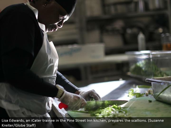 Lisa Edwards, an iCater learner in the Pine Street Inn kitchen, readies the scallions. (Suzanne Kreiter/Globe Staff)
