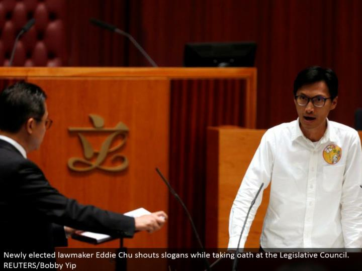 Newly chose administrator Eddie Chu yells mottos while taking vow at the Legislative Council. REUTERS/Bobby Yip