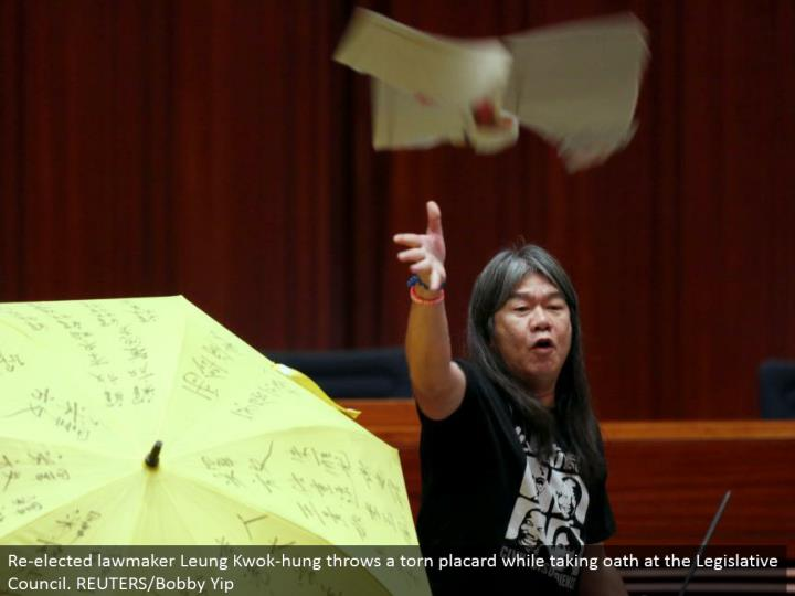 Re-chose official Leung Kwok-hung tosses a torn notice while taking pledge at the Legislative Council. REUTERS/Bobby Yip