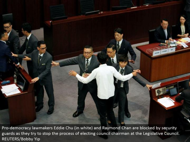 Pro-majority rules system officials Eddie Chu (in white) and Raymond Chan are obstructed by security monitors as they attempt to stop the way toward choosing gathering administrator at the Legislative Council. REUTERS/Bobby Yip