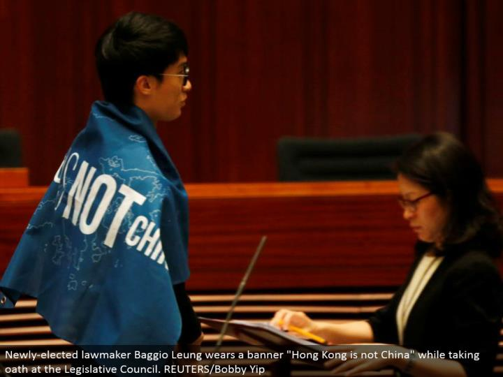 "Newly-chose official Baggio Leung wears a pennant ""Hong Kong is not China"" while taking promise at the Legislative Council. REUTERS/Bobby Yip"