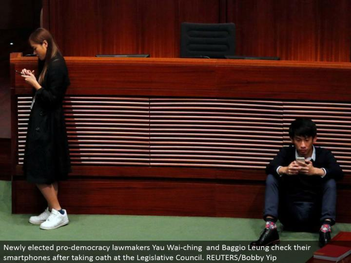 Newly chose professional majority rules system administrators Yau Wai-ching and Baggio Leung check their cell phones in the wake of taking pledge at the Legislative Council. REUTERS/Bobby Yip