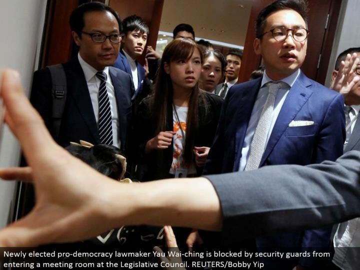 Newly chose star majority rules system legislator Yau Wai-ching is hindered by security protects from going into a meeting room at the Legislative Council. REUTERS/Bobby Yip