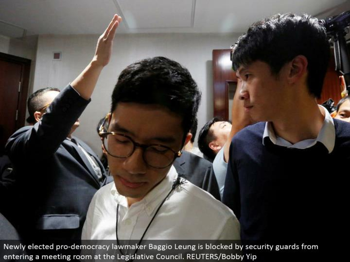 Newly chose expert vote based system administrator Baggio Leung is hindered by security monitors from going into a meeting room at the Legislative Council. REUTERS/Bobby Yip