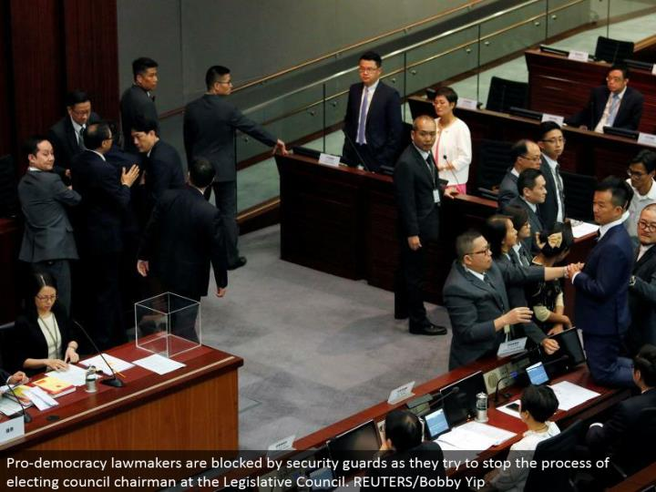 Pro-vote based system legislators are obstructed by security monitors as they attempt to stop the way toward choosing gathering executive at the Legislative Council. REUTERS/Bobby Yip