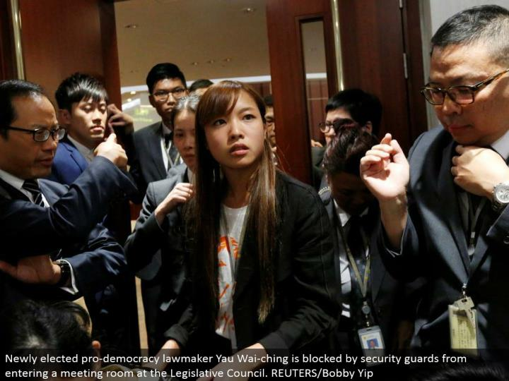 Newly chose professional majority rules system official Yau Wai-ching is hindered by security protects from going into a meeting room at the Legislative Council. REUTERS/Bobby Yip