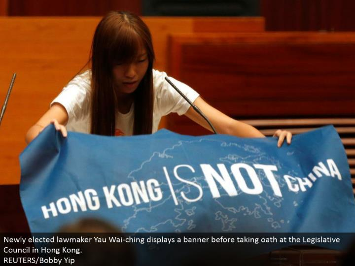 Newly chose administrator Yau Wai-ching shows a flag before taking vow at the Legislative Council in Hong Kong. REUTERS/Bobby Yip