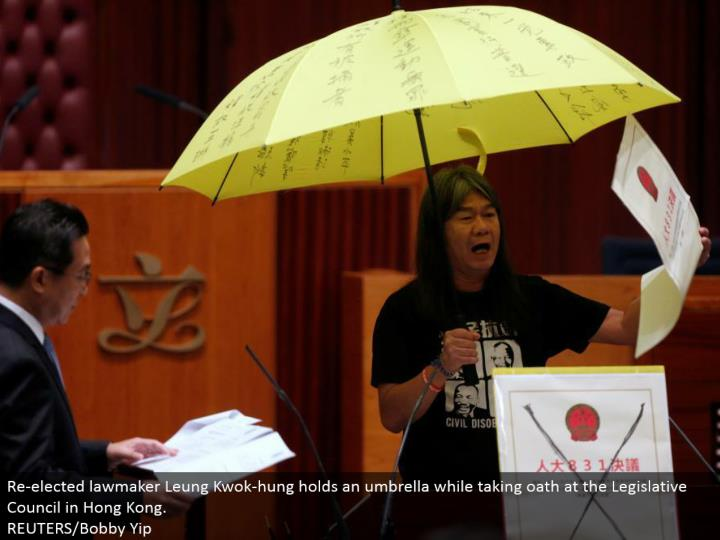 Re-chose legislator Leung Kwok-hung holds an umbrella while taking promise at the Legislative Council in Hong Kong. REUTERS/Bobby Yip