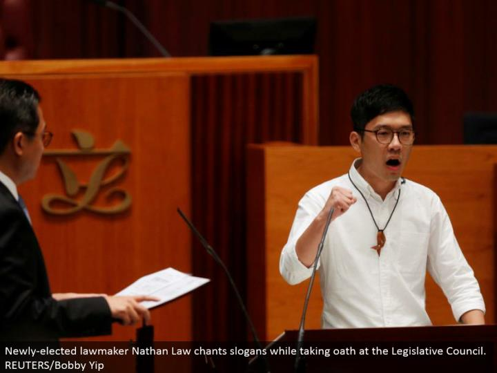 Newly-chose administrator Nathan Law serenades mottos while taking pledge at the Legislative Council. REUTERS/Bobby Yip