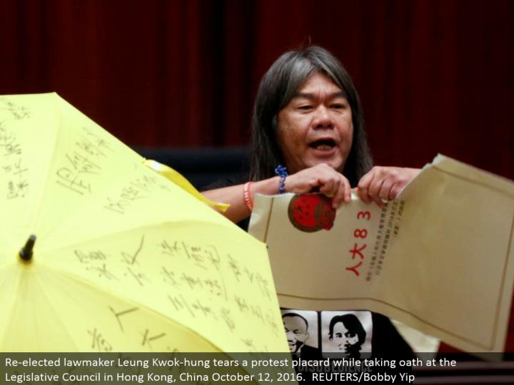 Re-chose administrator Leung Kwok-hung tears a challenge notice while taking vow at the Legislative Council in Hong Kong, China October 12, 2016. REUTERS/Bobby Yip