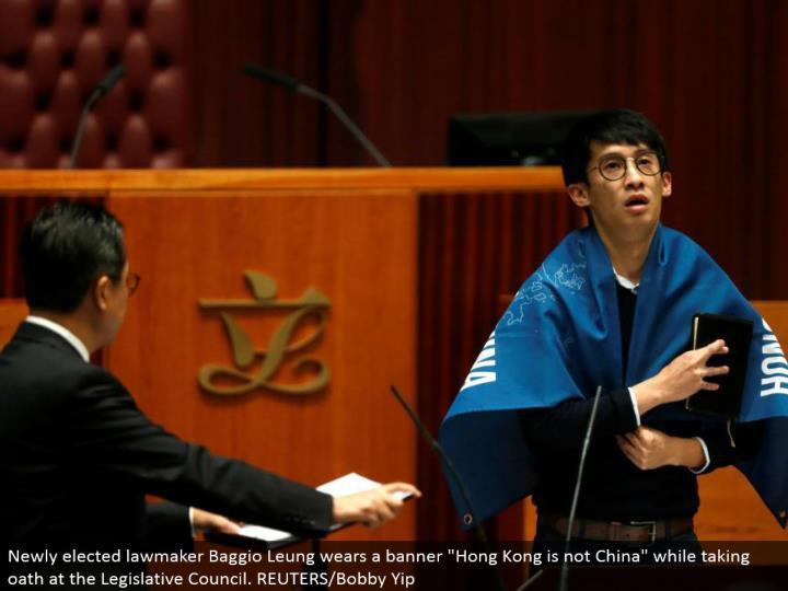 "Newly chose administrator Baggio Leung wears a flag ""Hong Kong is not China"" while taking pledge at the Legislative Council. REUTERS/Bobby Yip"