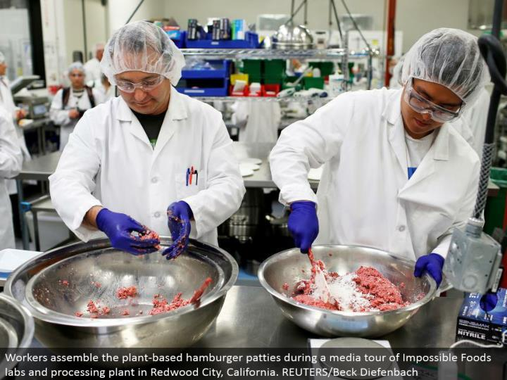Workers gather the plant-based ground sirloin sandwich patties amid a media voyage through Impossible Foods labs and handling plant in Redwood City, California. REUTERS/Beck Diefenbach
