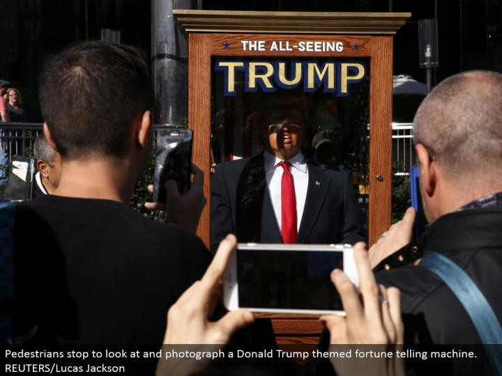 Pedestrians stop to take a gander at and photo a Donald Trump themed fortune telling machine. REUTERS/Lucas Jackson
