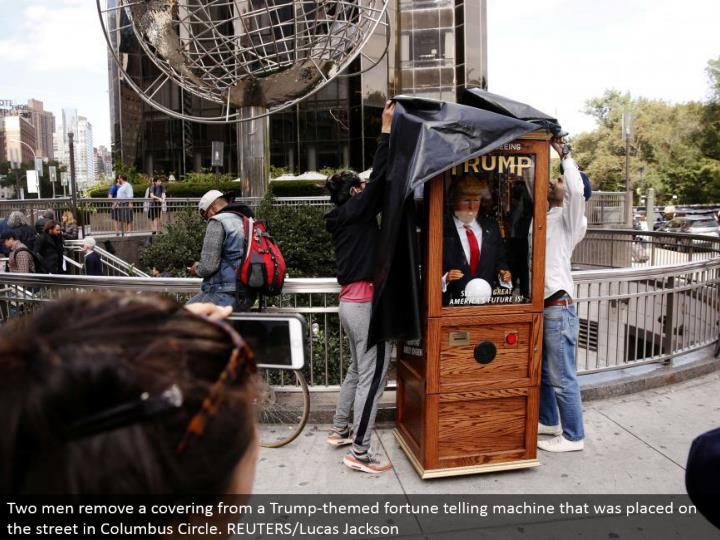 Two men expel a covering from a Trump-themed fortune telling machine that was put in the city in Columbus Circle. REUTERS/Lucas Jackson