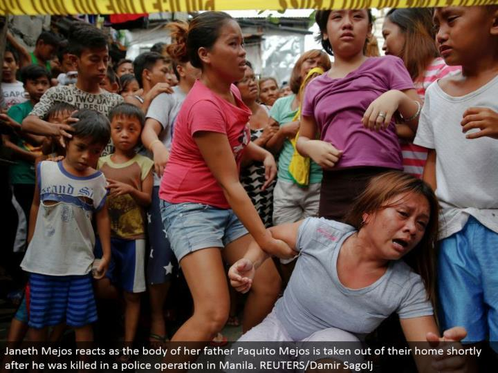 Janeth Mejos responds as the body of her dad Paquito Mejos is removed from their home soon after he was murdered in a police operation in Manila. REUTERS/Damir Sagolj