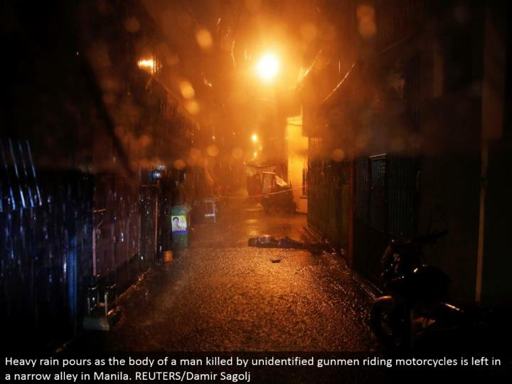 Heavy rain pours as the body of a man murdered by unidentified shooters riding cruisers is left in a limited back street in Manila. REUTERS/Damir Sagolj