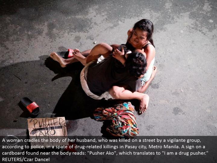 "A lady supports the body of her significant other, who was slaughtered on a road by a vigilante aggregate, as indicated by police, in a spate of medication related killings in Pasay city, Metro Manila. A sign on a cardboard found close to the body peruses: ""Pusher Ako"", which means ""I am a medication pusher."" REUTERS/Czar Dancel"
