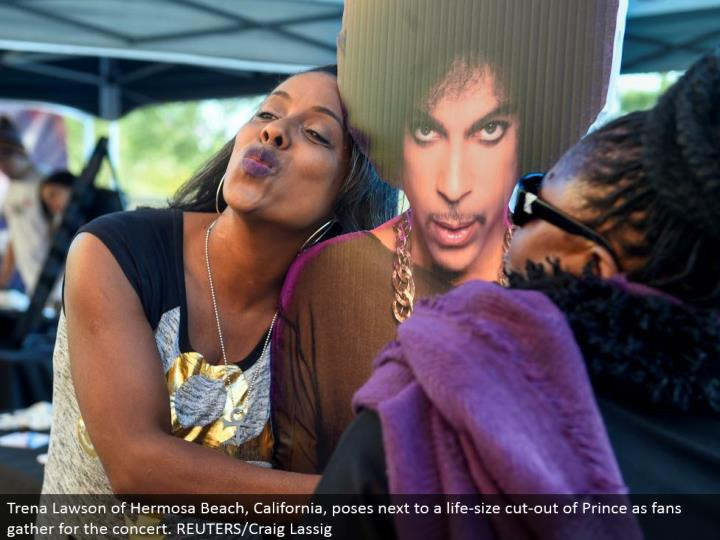 Trena Lawson of Hermosa Beach, California, postures alongside an existence measure cut-out of Prince as fans accumulate for the show. REUTERS/Craig Lassig