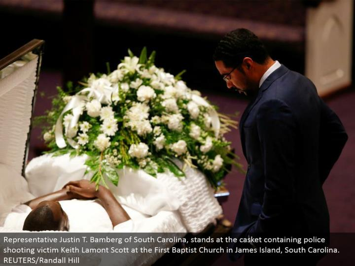 Representative Justin T. Bamberg of South Carolina, remains at the coffin containing police shooting casualty Keith Lamont Scott at the First Baptist Church in James Island, South Carolina. REUTERS/Randall Hill