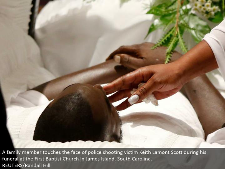 A relative touches the substance of police shooting casualty Keith Lamont Scott amid his memorial service at the First Baptist Church in James Island, South Carolina. REUTERS/Randall Hill