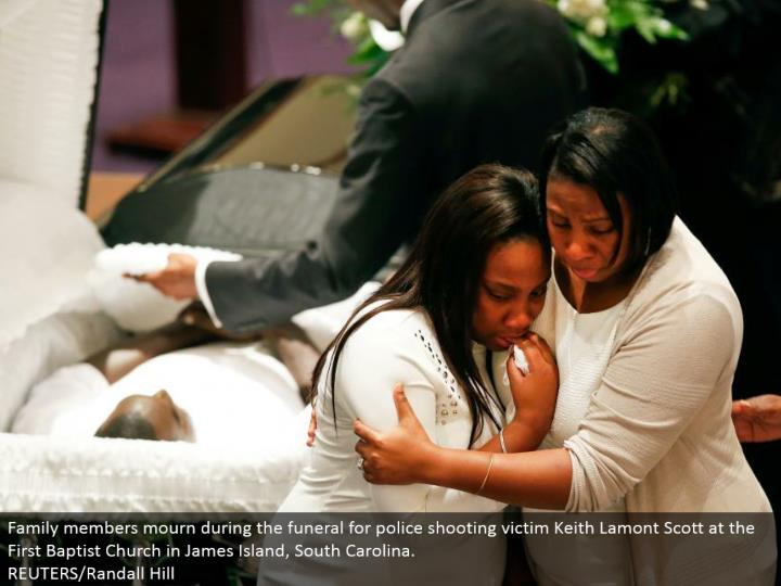 Family individuals grieve amid the memorial service for police shooting casualty Keith Lamont Scott at the First Baptist Church in James Island, South Carolina. REUTERS/Randall Hill