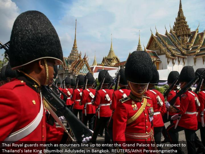 Thai Royal gatekeepers walk as grievers line up to enter the Grand Palace to pay regard to Thailand's late King Bhumibol Adulyadej in Bangkok. REUTERS/Athit Perawongmetha