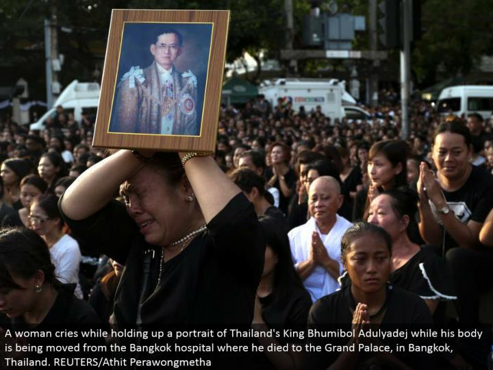 A lady cries while holding up a representation of Thailand's King Bhumibol Adulyadej while his body is being moved from the Bangkok healing center where he kicked the bucket to the Grand Palace, in Bangkok, Thailand. REUTERS/Athit Perawongmetha