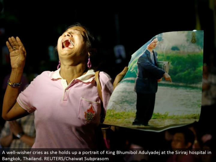 A well-wisher cries as she holds up a representation of King Bhumibol Adulyadej at the Siriraj healing facility in Bangkok, Thailand. REUTERS/Chaiwat Subprasom