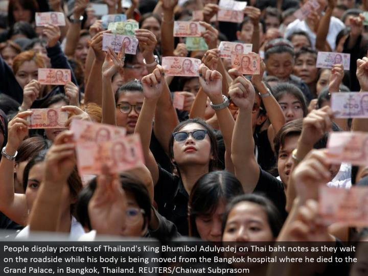 People show pictures of Thailand's King Bhumibol Adulyadej on Thai baht notes as they tend to the ro...