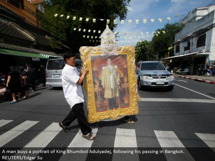 A man purchases a representation of King Bhumibol Adulyadej, taking after his going in Bangkok. REUTERS/Edgar Su