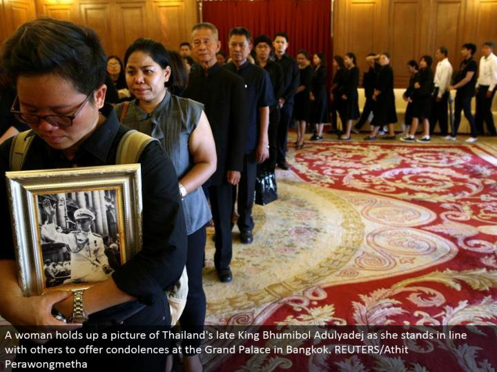 A lady holds up a photo of Thailand's late King Bhumibol Adulyadej as she stands in accordance with others to offer sympathies at the Grand Palace in Bangkok. REUTERS/Athit Perawongmetha