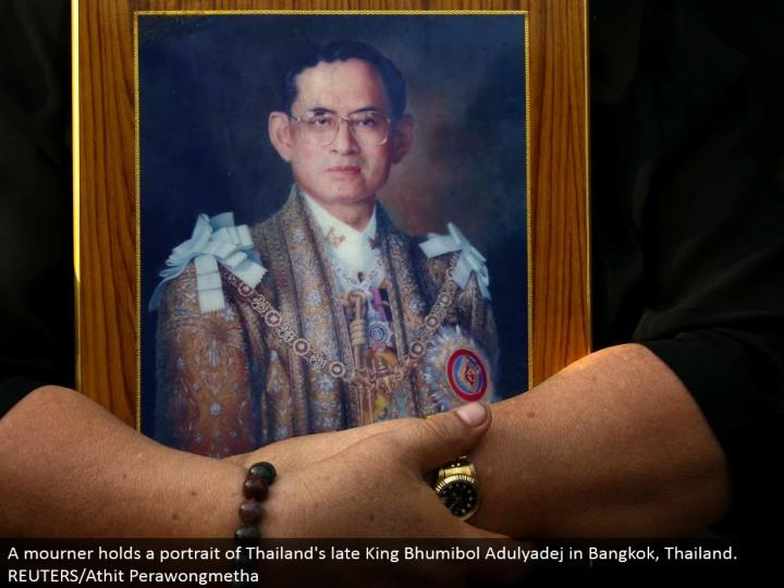 A griever holds a representation of Thailand's late King Bhumibol Adulyadej in Bangkok, Thailand. REUTERS/Athit Perawongmetha
