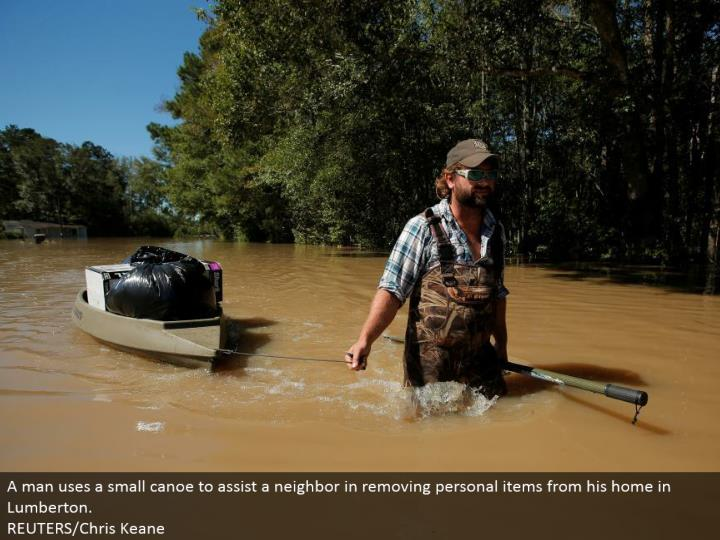 A man utilizes a little kayak to help a neighbor in expelling individual things from his home in Lumberton.  REUTERS/Chris Keane