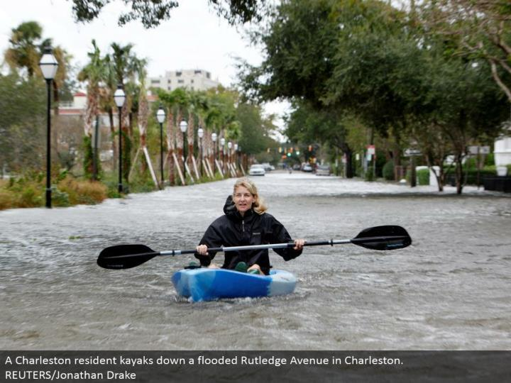 A Charleston inhabitant kayaks down an overwhelmed Rutledge Avenue in Charleston.  REUTERS/Jonathan Drake
