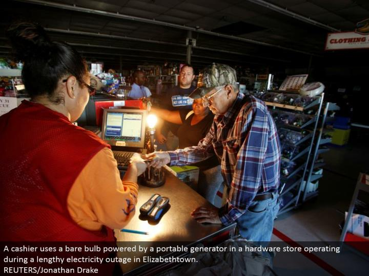 A clerk utilizes an exposed globule fueled by a compact generator in a handyman shop working amid a protracted power blackout in Elizabethtown.  REUTERS/Jonathan Drake