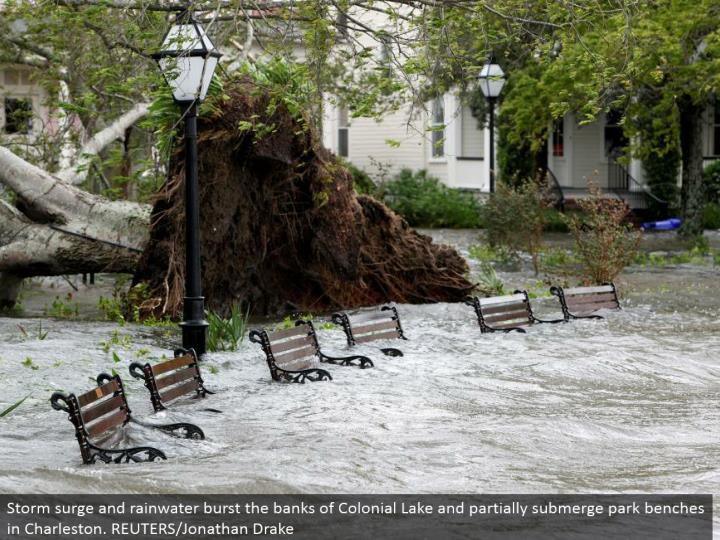 Storm surge and water burst the banks of Colonial Lake and in part submerge stop seats in Charleston. REUTERS/Jonathan Drake