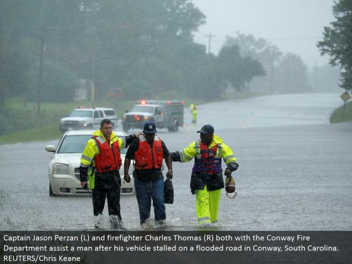 Captain Jason Perzan (L) and firefighter Charles Thomas (R) both with the Conway Fire Department help a man after his vehicle slowed down on an overwhelmed street in Conway, South Carolina. REUTERS/Chris Keane