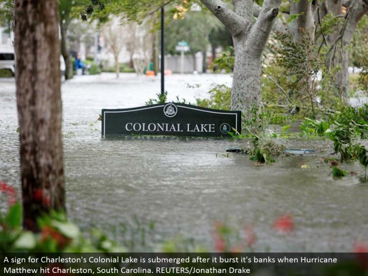 A sign for Charleston's Colonial Lake is submerged after it burst it's banks when Hurricane Matthew hit Charleston, South Carolina. REUTERS/Jonathan Drake