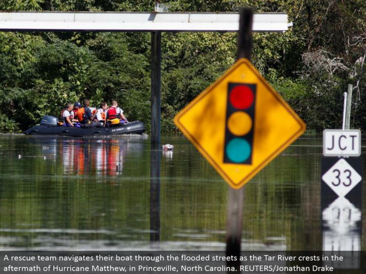A save group explores their pontoon through the overflowed roads as the Tar River peaks in the fallout of Hurricane Matthew, in Princeville, North Carolina. REUTERS/Jonathan Drake
