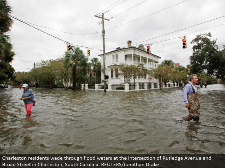 Charleston occupants swim through surge waters at the convergence of Rutledge Avenue and Broad Street in Charleston, South Carolina. REUTERS/Jonathan Drake