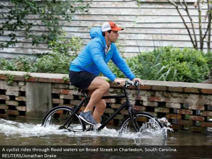 A cyclist rides through surge waters on Broad Street in Charleston, South Carolina. REUTERS/Jonathan Drake