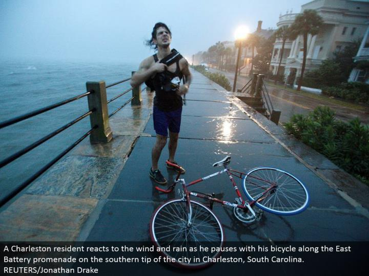 A Charleston occupant responds to the wind and rain as he stops with his bike along the East Battery promenade on the southern tip of the city in Charleston, South Carolina. REUTERS/Jonathan Drake