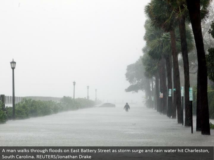 A man strolls through surges on East Battery Street as tempest surge and rain water hit Charleston, South Carolina. REUTERS/Jonathan Drake