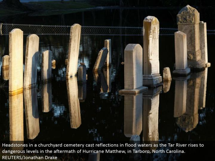 Headstones in a churchyard burial ground cast appearance in surge waters as the Tar River ascends to unsafe levels in the result of Hurricane Matthew, in Tarboro, North Carolina. REUTERS/Jonathan Drake