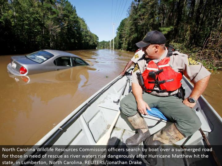 North Carolina Wildlife Resources Commission officers seek by vessel over a submerged street for those needing salvage as waterway waters rise hazardously after Hurricane Matthew hit the state, in Lumberton, North Carolina. REUTERS/Jonathan Drake