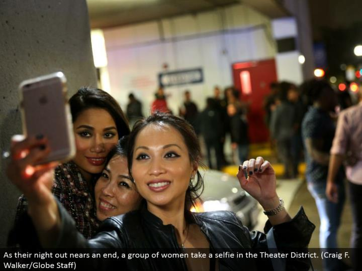 As their night out nears an end, a gathering of ladies take a selfie in the Theater District. (Craig F. Walker/Globe Staff)