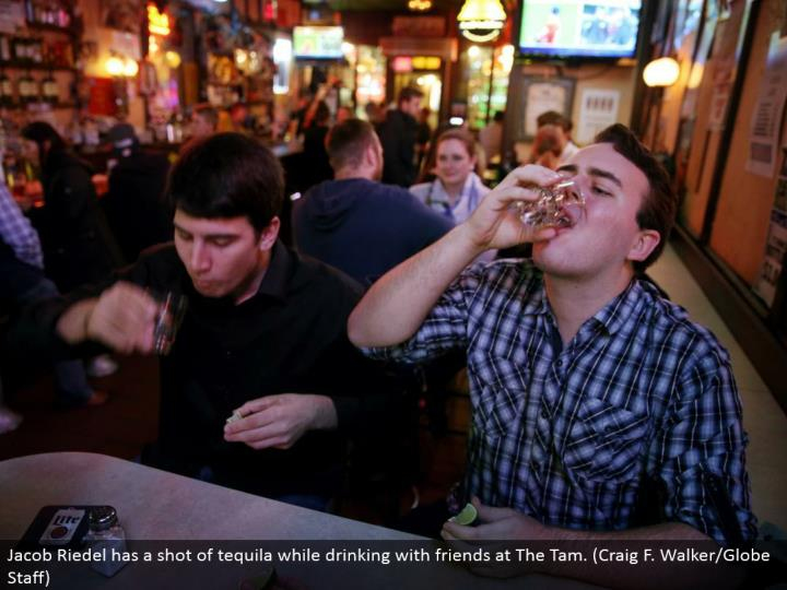Jacob Riedel has a dose of tequila while drinking with companions at The Tam. (Craig F. Walker/Globe Staff)