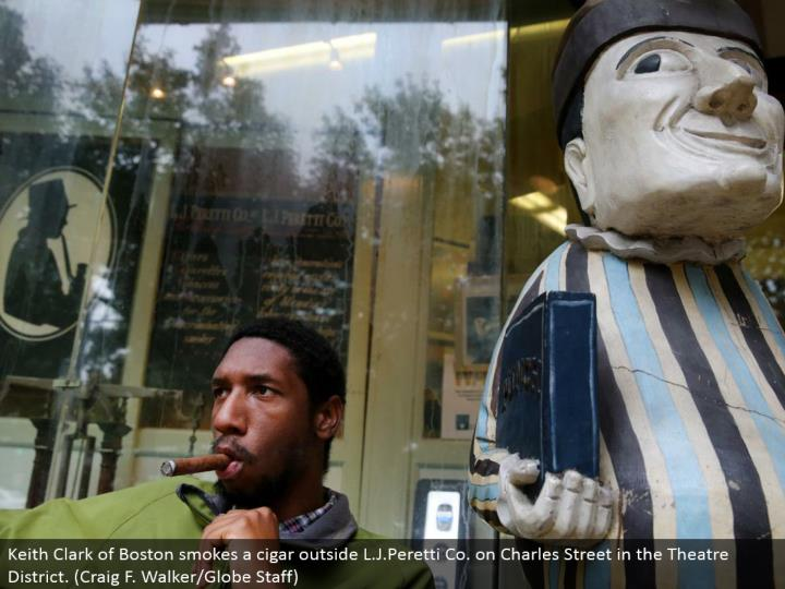 Keith Clark of Boston smokes a stogie outside L.J.Peretti Co. on Charles Street in the Theater District. (Craig F. Walker/Globe Staff)
